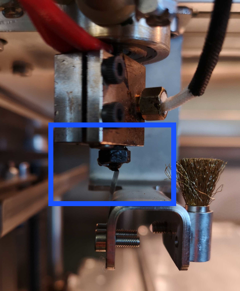 The tip of the blade should just touch the tip of the nozzle.